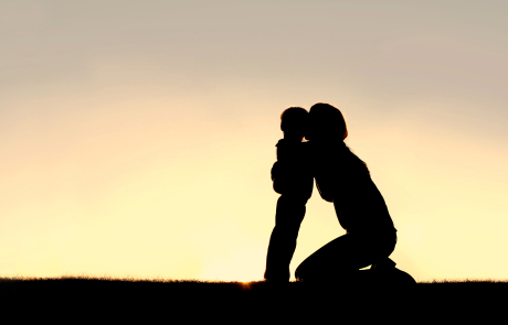 Silhouette of Young Mother Hugging Toddler Son at Sunset